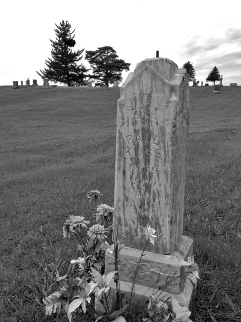 The grave of Paul Kuss in Otisco Cemetery, Minnesota. The tiny gravestones in the background are in the main cemetery. Paul Kuss committed suicide in 1910 and thus is buried in unconsecrated ground. Someone still cares, though--note the flowers.